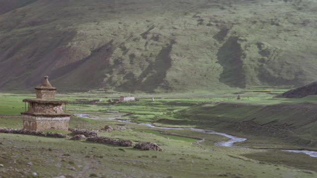 MEDIUM ANGLE OF FLOOR OF VALLEY WITH STREAM RUNNING IN CENTER. SEE SHRINE ON LEFT, TWO PEOPLE RUN TOWARD STREAM AND DUCK BEHIND ROW OF ROCKS. HILL COVERED WITH GRASS IN BACKGROUND.