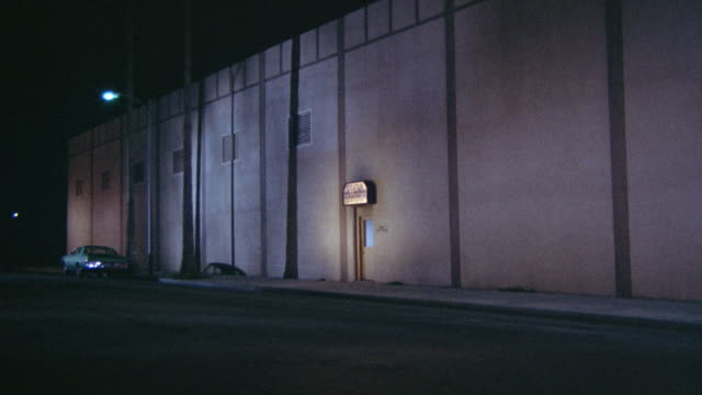 MEDIUM ANGLE ESTABLISH OF SIDE OF INDUSTRIAL AREA WAREHOUSE. SEE CONCRETE WALLS WITH SIX POSSIBLE WINDOWS. SEE SMALL DOOR AT FRAME CENTER. SEE EMPTY STREET EXCEPT FOR ONE PARKED CAR AT FRAME LEFT. SEE SINGLE LIT STREET LIGHT.