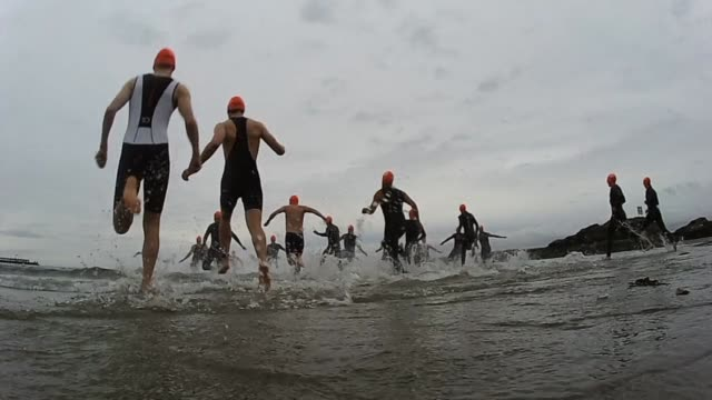 triathlon swim start into waves slow motion - salmini stock videos and b-roll footage