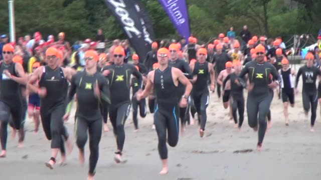 triathlon swim start participants charge down beach into water - salmini stock videos and b-roll footage
