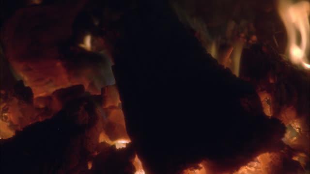 vídeos de stock, filmes e b-roll de close angle of wood burning in fire, coals. flames. - carvão
