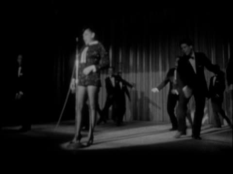 Entertainer Judy Garland wearing long black evening gown taking stage for performance at nightclub / Male dancers in matching black tuxedos hold...