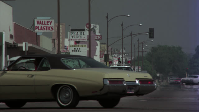 wide angle of city street traffic. camper truck drives by, followed by police car.  camera follows police car r-l and stops on coffe shop restaurant and drive-in. sign displays 'arthur's.' another sign above is a triple sided large letter   'a'. this burb - 1975 stock videos and b-roll footage