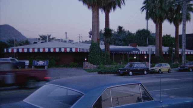 wide angle of maison gerard restaurant. cmi to entrance. lights on. cars drive by with headlights and tail lights on. cars parked in front. palms tree out front mountains in bg. red and white canopy over restaurant. - 1977年点の映像素材/bロール