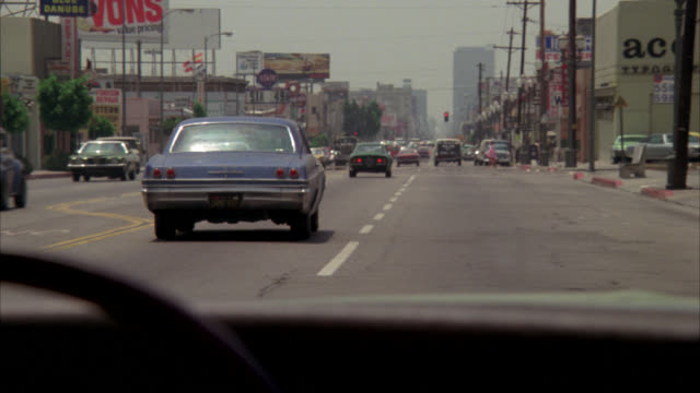 wide angle driving pov forward. city streets. light city traffic. drivers face visible in rear view mirror - anno 1975 video stock e b–roll