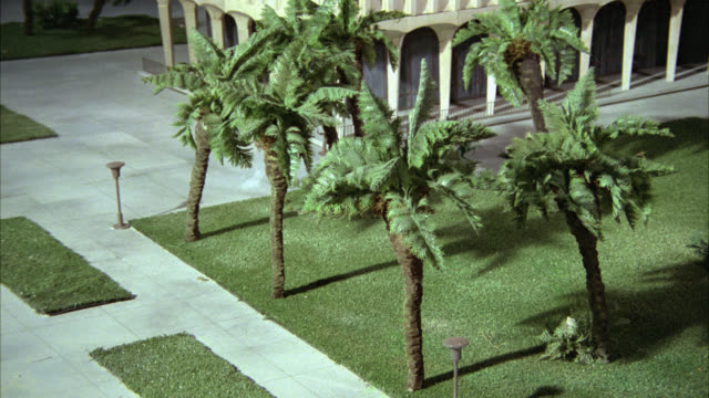 medium angle of model or miniature palm trees and grass in front of hotel or apartment building. bright flash occurs and wind rocks trees. could be natural disaster, war, or atomic bomb. miniature models. - nuclear bomb stock videos & royalty-free footage