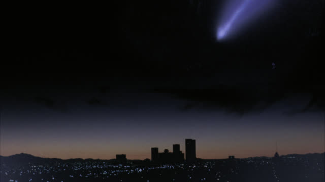wide angle of city skyline at night as  asteroid or meteor falls from sky and lands at horizon. could be atomic bomb. - 彗星点の映像素材/bロール