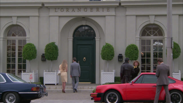 "WIDE ANLGEO OF PEOPLE ENTERING BUILDING WITH ""L'ORANGERIE"" ABOVE ENTRANCE. COULD BE COUNTRY CLUB OR UPPER CLASS RESTAURANT. LUXURY CARS PARKED IN FRONT OF BUILDING."