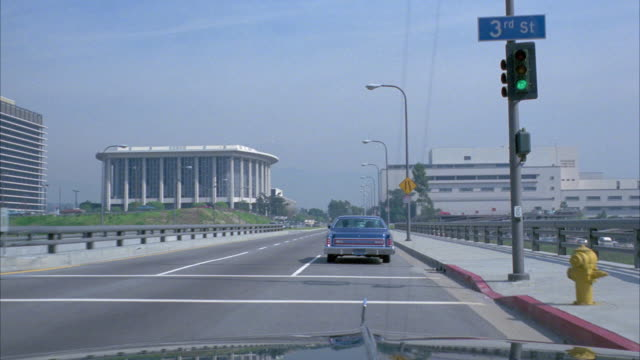 wide angle moving pov straight ahead / inside car pov / driving along street bridge / see office buildings in bg - 1978 stock videos & royalty-free footage