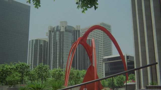 ESTABLISH MEDIUM ANGLE OF RED FOUR ARCHES SCULPTURE IN DOWNTOWN, BUNKER HILL. ART. BANK OF AMERICA PLAZA. SKYSCRAPERS AND OFFICE BUILDINGS IN BG.