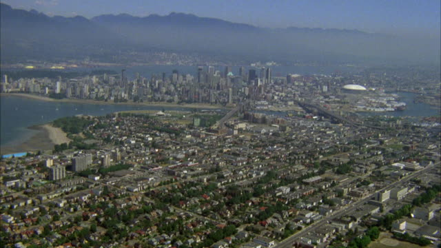 aerial over suburbs, residential area west of downtown vancouver. high rise office buildings and condominiums visible in distance. harbor, bay, frazier park and mountains visible in background. sky is hazy. - vancouver canada stock videos & royalty-free footage