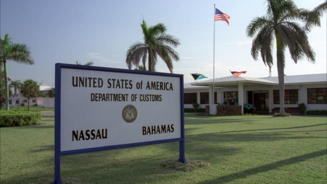 vídeos de stock e filmes b-roll de medium angle of us customs in nassau bahamas. sign reads united states of america department of customs nassau bahamas. one story building in bg. many palm trees tropical island. american and bahamian flags flying. jeep approached building in bg. - bahamas