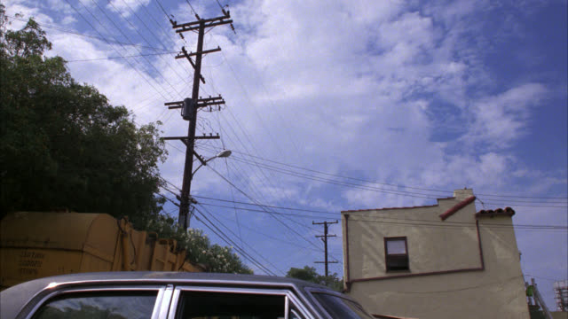 up angle of  blue cadillac flying thru air and over parked car. blue sky and clouds. telephone poles and wires. apartment building visible in bg. car stunts. - 1984 stock videos & royalty-free footage