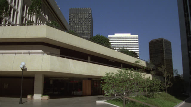 "up angle of twin office building high rises in downtown los angeles or century city. rolls royce convertible car pulls into courtyard area. could be executive. sign on building reads ""jonathan hart industries"" - century city stock-videos und b-roll-filmmaterial"