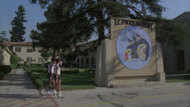 """pan right to left to """"l.c. police academy"""" sign and emblem to courtyard. recruits training in courtyard. police officers walking on sidewalk. - rekrut stock-videos und b-roll-filmmaterial"""