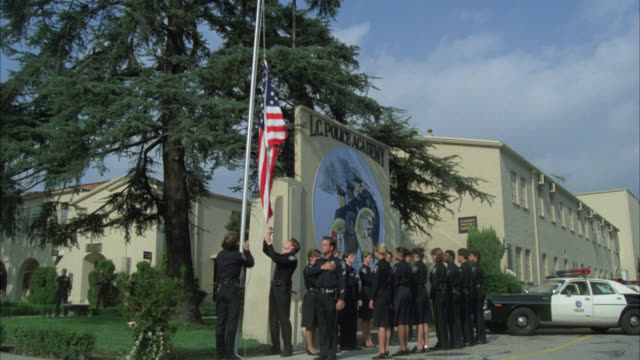 """wide angle of """"lc police academy"""" sign and emblem. police officers or recruits in uniforms raise american flag on flag pole. barracks in bg. police car in parking lot in bg. - fahnenstange stock-videos und b-roll-filmmaterial"""