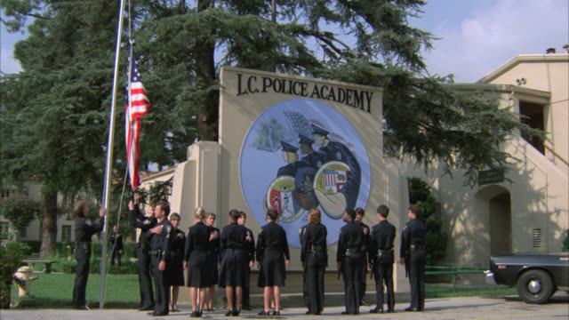 """wide angle of """"lc police academy"""" sign and emblem. police officers or recruits in uniforms raise american flag on flag pole. barracks in bg. police car in parking lot in bg. - barracks stock videos & royalty-free footage"""