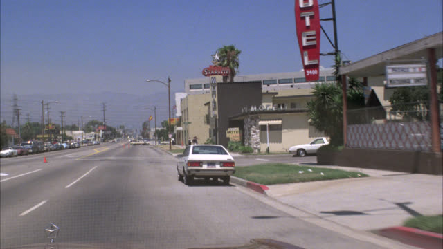 hand held moving pov driving down city street past starlite motel - 1984 stock videos & royalty-free footage