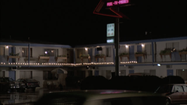"""pan down est motel sign """"bel air palms motel""""  pan down to two story white motel and front window of black car across the street. wet pavement indicates possible rain shower earlier. - wet wet wet stock videos & royalty-free footage"""