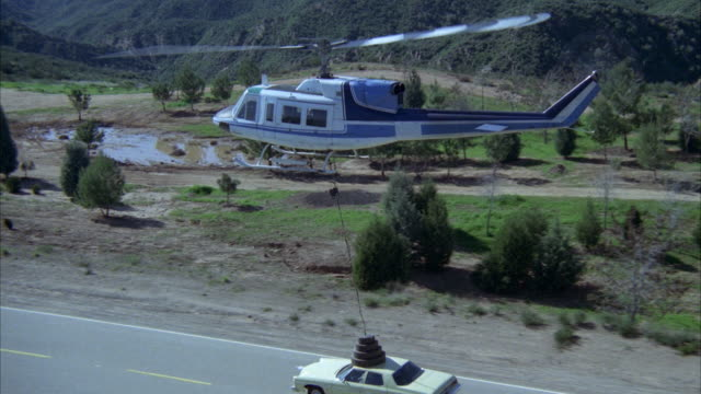 wide angle of blue and white helicopter with magnet attached flies over yellow car on two lane mountain road.  helicopter picks up car and flies with it r-l. neg cuts helicopter flies to bg and mountains  cpb to show a man and a woman standing by side of - magnet stock videos & royalty-free footage