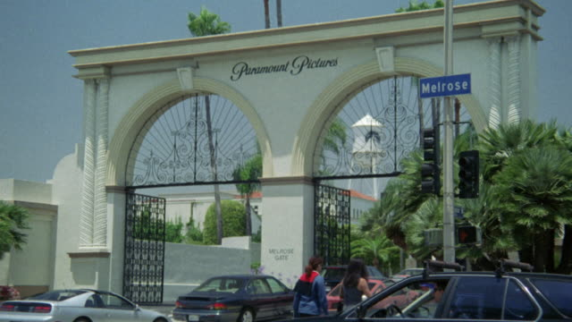 wide angle of paramount pictures studio entrance gate. zoom in on melrose street sign. cars waiting in line at gate. - paramount studios stock videos & royalty-free footage