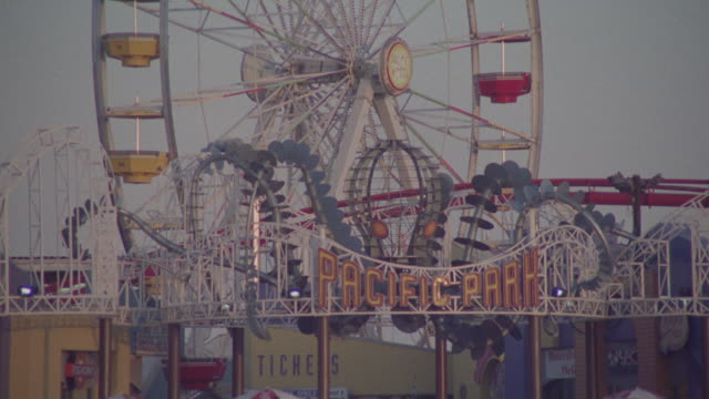 """pan down from sky to ferris wheel and roller coaster. sign reads """"pacific park"""". people in line for the ride. santa monica pier. los angeles area. - santa monica sign stock videos & royalty-free footage"""