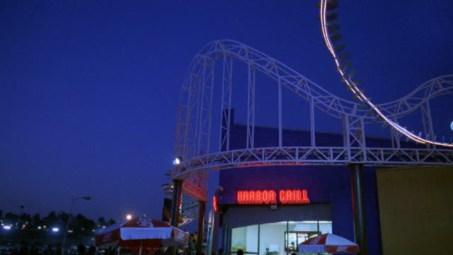 """pan left to right from """"harbor grill"""" restaurant, to """"pacific park"""" neon sign. amusement park. santa monica pier. los angeles area. roller-coaster in bg. - santa monica sign stock videos & royalty-free footage"""
