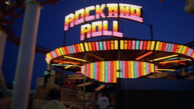 """cam pans up from """"rock n roll"""" neon sign and carousel, merry-go-round or ride to ferris wheel. santa monica pier. amusement park. los angeles area. - santa monica pier sign stock videos & royalty-free footage"""