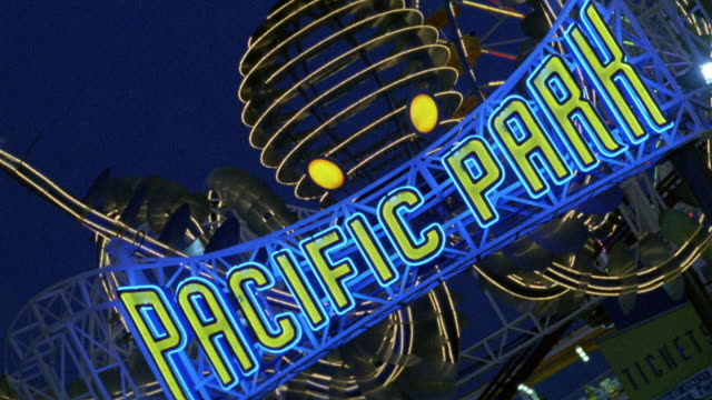 """medium angle of a neon sign that reads """"pacific park"""". see many lights around. santa monica pier. roller coaster. amusement park. los angeles area. - santa monica pier sign stock videos & royalty-free footage"""