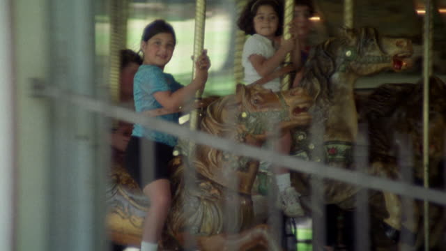 pan left to right following girl or child on a wooden horse on merry-go-round or carousel. griffith park. - carousel horse stock videos and b-roll footage