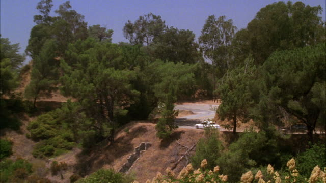 pan right to left wide angle of white lincoln town car being chased or pursuded by black lincoln town car on winding mountain road lined with trees. griffith park. car chases. cars swerve around corner. - lincoln town car stock videos and b-roll footage