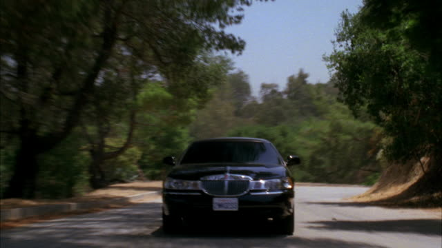 tracking shot of black lincoln town car driving up winding mountain road in griffith park. could be car chase or pursuit. - lincoln town car stock videos and b-roll footage