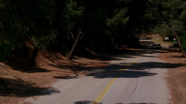 wide angle of rural area or mountain road lined with trees. white lincoln town car drives up road being pursued or chased by black lincoln town car. cars rapidly do 180 and turn around colliding with each other. - lincoln town car stock videos and b-roll footage