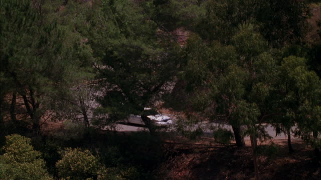 pan left to right wide angle of white lincoln town car being chased or pursuded by black lincoln town car on winding mountain road lined with trees. griffith park. car chases. - lincoln town car stock videos & royalty-free footage