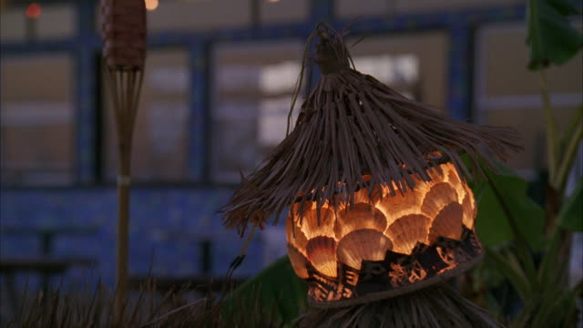 stockvideo's en b-roll-footage met pan up from beach lamp made of sea shells and straw with restaurant and tiki torch in bg to apartment building hotel in bg. - tiki torch