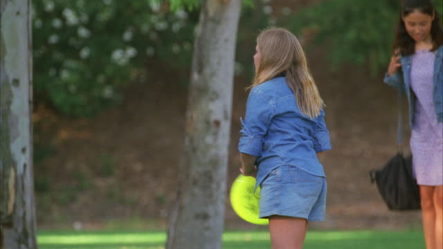 medium angle of teenagers, young women playing frisbee in park. other teenagers or students, children, in bg with backpacks. could be on campus of school or in park. trees and bushes. - kinderspielplatz stock-videos und b-roll-filmmaterial