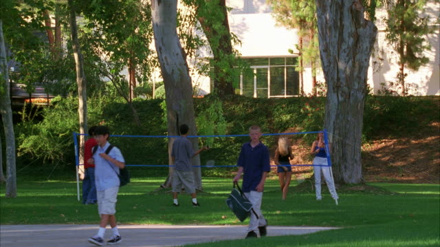 wide angle of teenagers playing badminton in the park. see other children or teenagers walking in fg. lawn and trees with white building in bg. could be park playground. - city of los angeles stock-videos und b-roll-filmmaterial
