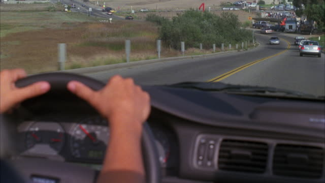 vídeos de stock e filmes b-roll de wide angle driving pov over steering wheel, in convertible car. highway or street through rural area or countryside. could be pacific coast highway near malibu. woman with blonde hair driving. - 1995