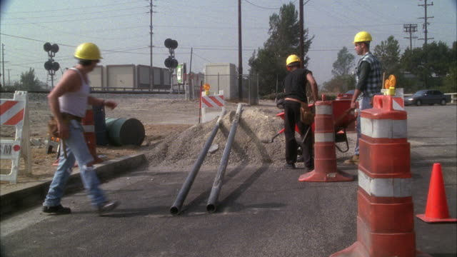 MEDIUM ANGLE MOVING POV TOWARD THREE CONSTRUCTION WORKERS WORKING WITH SHOVELS NEXT TO GRAVEL PILE. WORKERS DROP TOOLS AND SCATTER AS, PANIC OR EMERGENCY. COULD BE RUNNING FROM CAR OR VEHICLE. ORANGE CONES OR BARRICADES. COULD BE BURBANK.