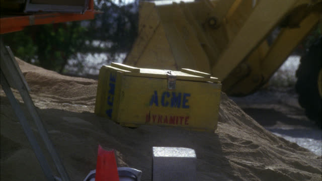 "medium angle of yellow wooden box of ""acme dynamite"" sitting on dirt pile in construction site. orange dumpster tips over from left onto box causing an explosion. fires and flames. bull dozer visible. - explosive stock videos & royalty-free footage"