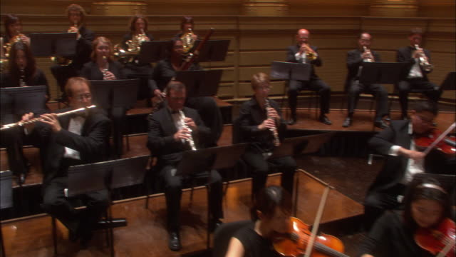 wide angle of concert hall with orchestra playing on stage. could be theater. camera pans over violinists, and bassists to flautists, french horn players, clarinet players, and oboe player. timpanist in bg. music stands. - concert hall stock videos and b-roll footage