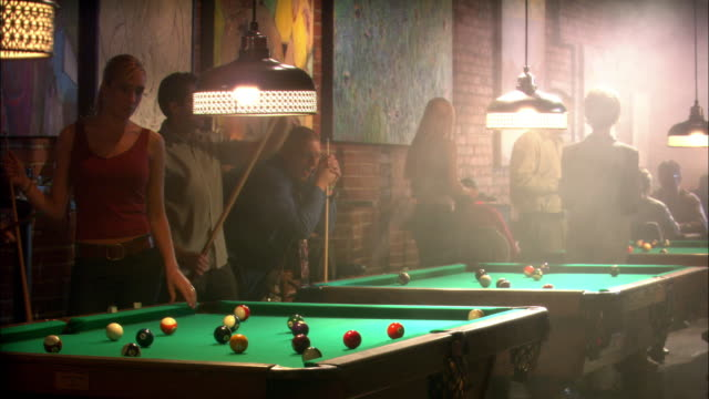 wide angle of billiard or pool hall.  people playing pool with dim lighting. waitress walks by camera with tray. could be bar. - pool hall stock videos and b-roll footage