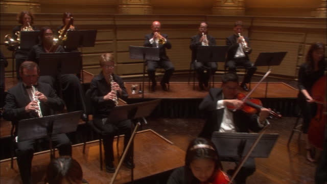 wide angle of concert hall with orchestra playing on stage. could be theater. camera pans over violinists, and bassists to flautists, french horn players, clarinet players, and oboe player. timpanist in bg. music stands. - french horn stock videos and b-roll footage