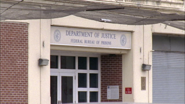 WIDE ANGLE OF DEPARTMENT OF JUSTICE FEDERAL BUREAU OF PRISONS SIGN OF THE ENTRANCE TO THE BRICK BUILDING.