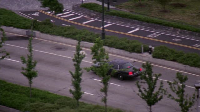 HIGH ANGLE DOWN OF DARK BLUE FORD CROWN VICTORIA DRIVING DOWN THE HENRY HUDSON PARKWAY. CAMERA FOLLOWS CAR.