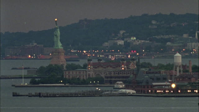 wide angle of ellis island. statue of liberty on the left side with torch lit.  liberty island in the background. - new york harbor stock videos & royalty-free footage