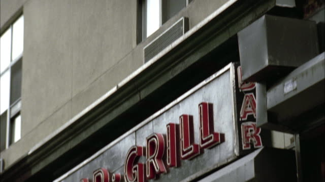 """pan down from window to """"bar and grill"""" neon sign. restaurant. down to double door entrance at street level. people walking and standing in front of door. - bar点の映像素材/bロール"""