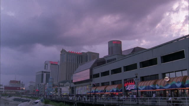vídeos de stock, filmes e b-roll de wide angle on the boardwalk in atlantic city. high rise in bg. camera pans r-l then l-r numerous times as people walk along the boardwalk. see signs for caesars and bally's hotel and casino. - atlantic city