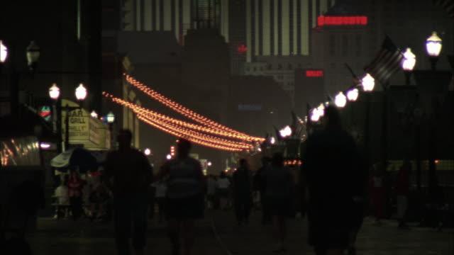 vídeos de stock, filmes e b-roll de medium angle on people walking down the boardwalk at atlantic city. - atlantic city