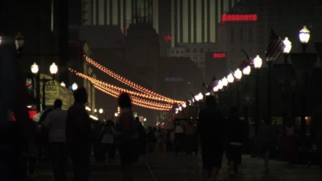 vidéos et rushes de wide angle on the taj mahal casino hotel. camera pans down to people walking along the boardwalk at atlantic city. - allée couverte de planches